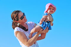 Beach Play Child Mother. A smiling child and her mother play together on a sunny day Royalty Free Stock Photos