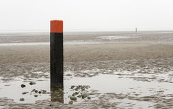 Beach pole on wet sand Royalty Free Stock Photo