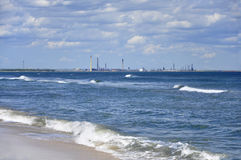 Beach with polluting industry in background Royalty Free Stock Photo