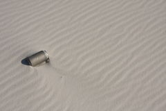 Beach pollution. An old lost silver can lying in the sand. Pollution concept Royalty Free Stock Photo