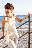The beach pose. A beautiful model with dark brown hair wearing a silk one piece standing against the railing of the stairs with the beach in the background stock photography
