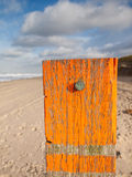 Beach post with sea level marker with beach and sea behind Royalty Free Stock Image