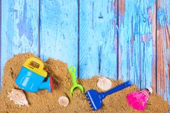 Beach poster with sand and toys. Beach poster on wooden background with sand and plastic toys Stock Images