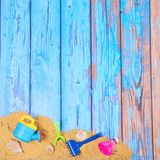 Beach poster with sand and toys. Beach poster on wooden background with sand and plastic toys Royalty Free Stock Photo