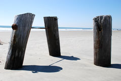 Beach Posts. A series of three wooden posts sticking up out of the beach Royalty Free Stock Photo