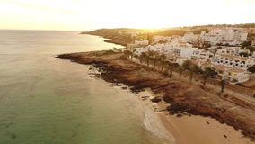 Beach of Praia da Luz at sunset, Lagos, Algarve, Portugal aerial view stock video footage