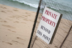 Beach Private Property Sign. Sign on wire fence posting beach area closed to public. Sand and water blurred in background. Medium view. Horizontal format Royalty Free Stock Photography