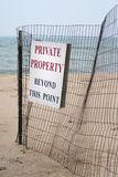 Beach Private Property Sign. Sign on wire fence posting beach area closed to public. Sand and water blurred in background. Medium view. Vertical format Stock Photo