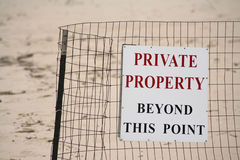 Beach Private Property Sign. Sign on wire fence posting beach area closed to public, against sand blurred in background. Horizontal format Royalty Free Stock Image