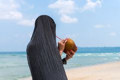 Beach profile girl drinking a coconut fresh cocktail in tropical sea. A girl in a gray shawl drinks coconut milk through a straw on a beautiful beach. Tropical Royalty Free Stock Photos