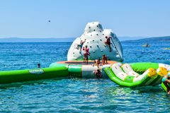 Beach in Promajna, Croatia. Promajna, Croatia - July 11, 2018: Vacationers on an entertainment slide stock image