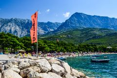 Beach in Promajna, Croatia. Promajna, Croatia - July 11, 2018: Vacationers on the public beach of the town of Promajna stock image