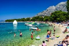Beach in Promajna, Croatia. Promajna, Croatia - July 11, 2018: Vacationers on the public beach of the town of Promajna royalty free stock photography