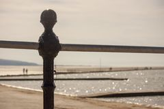 Beach promenade on a sunny afternoon. Railings along the prom on a seaside resort, West Kirby in the UK. With a view of the marine lake and beach royalty free stock photography