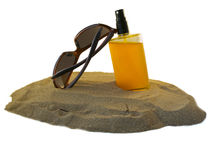 Beach protection. Sunglasses and sunoil on the beach Royalty Free Stock Images