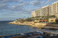 Beach and public park at Sliema on Malta. Rock beach, sea and public park at Sliema on Malta in late Autumn Royalty Free Stock Photo