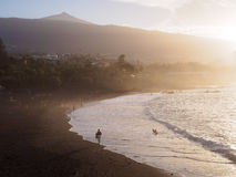 Beach in Puerto de la Cruz. Black sand beach in Puerto de la Cruz by the sunset with Teide volcano in the backround, Tenerife, Canary Islands Spain royalty free stock image