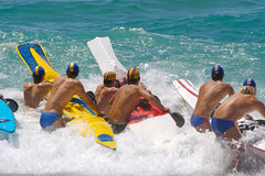 Beach race. Iron man, surf lifesaving race. Contestants holding their boats waiting to start Royalty Free Stock Image