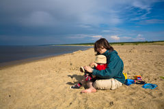 On the beach after the rain. Mom with a son on the beach after the rain Stock Images