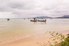 Beach on rainy season with some local fishing boats Stock Photos