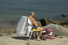 Beach Reading. An elderly gentleman sits in his beach chair reading Royalty Free Stock Images