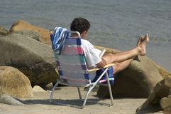 Beach Reading. A gentleman sitting in his beach chair reading, on the rocks Stock Photo