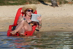 Woman with tablet. Enjoying the sunshine with my tablet while reading from my tablet Royalty Free Stock Photo