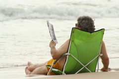 Beach Reading Too. A middle aged man sits in a beach chair and reads a magazine in the surf Stock Photo