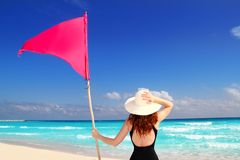 Beach rear woman holding red beach flag pole. Girl with swimming suit holding red beach flag pole rear view in Caribbean sea Royalty Free Stock Image