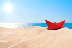 On the Beach - red paper boat on a sand dune Royalty Free Stock Image