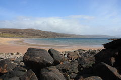 The Beach at Red Point with Rocks. This is an image of the beach at Red Point in the North west of Scotland. In the foreground are rocks, with a crescent shaped Royalty Free Stock Photography