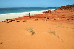 Beach with red rocks. Blue clear sky over the red rocks on a long sandy beach. Australian Royalty Free Stock Photography