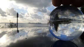 Beach reflected in crystal sphere white car sunrise. Crystal ball sitting on roof of white car acting as a mirror thru the crystsl ball reflecting the sky with Stock Photo