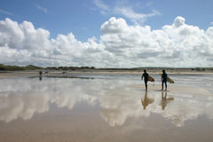 Beach reflections. And surfers, Gwithian Towans, Cornwall, UK Royalty Free Stock Photo