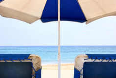 Beach Relaxation. View of the beach and sea from behind a beach umbrella and sun lougers Stock Images