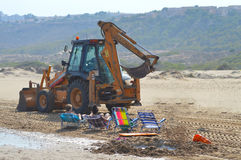 Beach Repairs - JCB CAT Digger At Seaside With Sunbathers And Holidaymakers Stock Photos