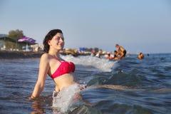 Beach resort, caucasian girl resting, sitting on surf line. Stock Image