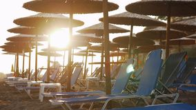 Empty chaise longues on resort and people leaving beach at sunset. Beach on resort with many empty chaise longues under straw umbrellas. People leaving seaside stock footage