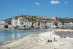 Beach resort with tourists and residential hill homes. SANTA PONSA, MALLORCA, SPAIN - MAY 10, 2018: Beach resort with tourists and residential homes on the hill Stock Photos