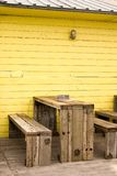 Beach restaurant. Wood seating of a beach restaurant against a yellow painted wall Stock Photos