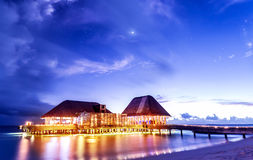 Beach restaurant in the night. Beach restaurant glowing with bright lights in the night, romantic place for date on tropical island, summer holidays concept stock images