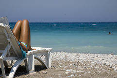 Beach in Rhodes - Greece. View of a beach with female legs in the foreground Royalty Free Stock Image