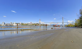 Beach, river and city at springtime Stock Images