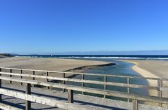 Beach with river, wooden handrail and seagulls. Golden sand and sea with waves and white foam. Sunny day. Galicia, Spain. Arteijo, La Coruna Province, Rias stock photos