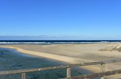 Beach with river, wooden handrail and waves. Blue sky, sunny day, Galicia, Spain. Galicia, La Coruña Province, Rias Altas, Spain. Beach with waves and river royalty free stock photo