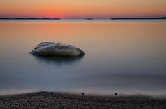 Beach with rock at sunrise Stock Image