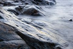 Beach Rocks. Water blurred by long exposure Royalty Free Stock Photo