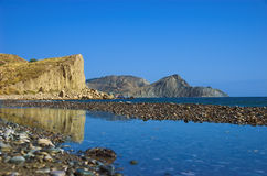 Beach and rocks. Reflecting in calm water, Eastern Crimea, Ukraine stock photos