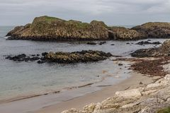 Beach and rocks in Ballintoy Harbour. Moyle, Northern Ireland, UK royalty free stock images