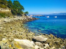 Beach of rocks in Cies Islands, Galicia, Spain, with boats diving in front of it royalty free stock images